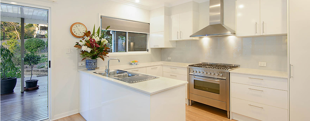Modern white kitchen with gas stove in Taringa